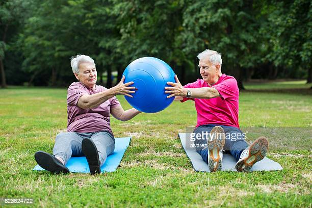 senior couple exercising with pilates ball at park - passing sport stockfoto's en -beelden