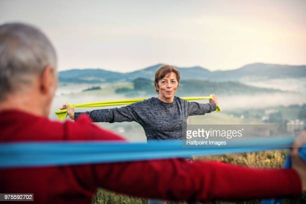 senior couple exercising with resistance bands outdoors in nature in the foggy morning. - gummihose stock-fotos und bilder