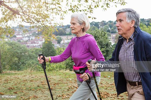 senior couple exercising,walking through parkland - purple shirt stock photos and pictures