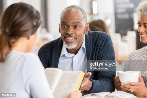 A senior couple explain Bible passage to young woman