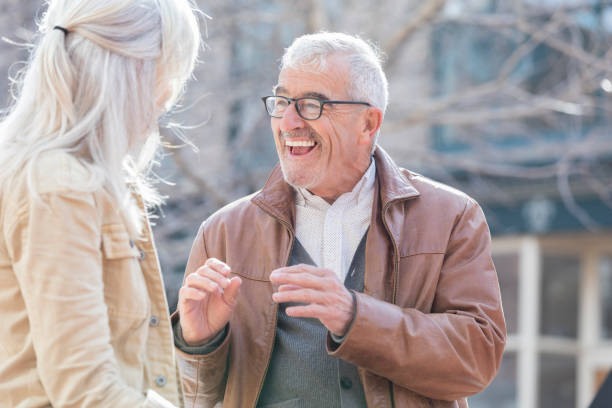 senior couple explore a city while on vacation - old man story telling stock pictures, royalty-free photos & images