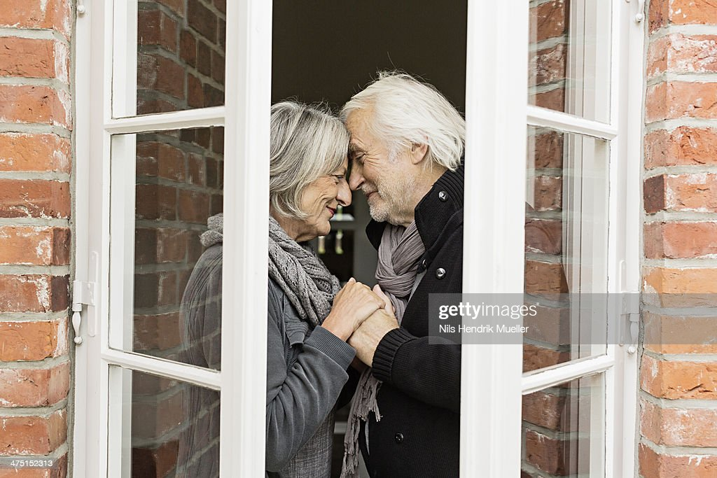 Senior couple face to face by window : Stock Photo