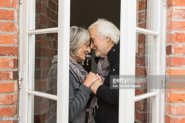 Senior couple face to face by window