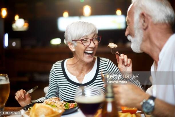 senior couple feeding each other and having a good time during a meal in a restaurant - dating stock pictures, royalty-free photos & images