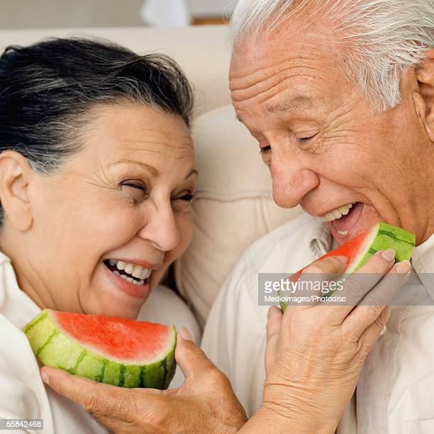 Senior couple feeding watermelon to each other, close-up