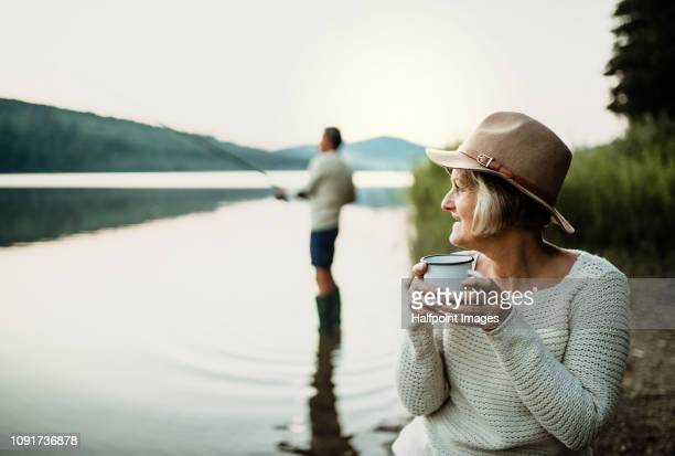 a senior couple fishing on a lake at sunset. - retirement stock pictures, royalty-free photos & images