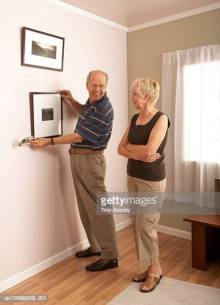 senior couple fixing paintings on wall - putting stock pictures, royalty-free photos & images