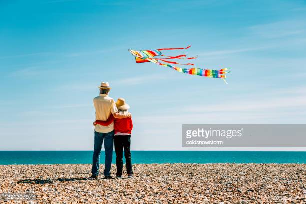 senior couple flying colorful rainbow kite at beach - beach stock pictures, royalty-free photos & images