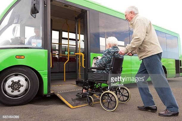 Senior Couple Getting on Bus Via Wheelchair Ramp