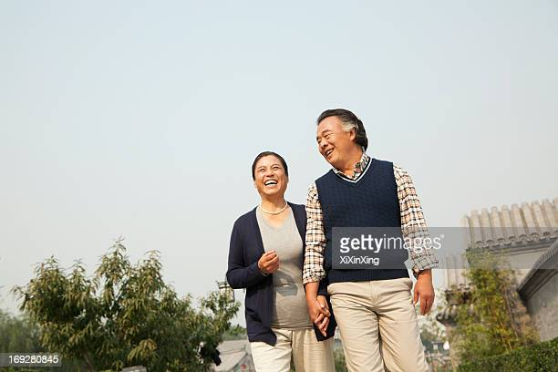 senior couple going for a stroll in beijing, holding hands - chinese culture stock pictures, royalty-free photos & images