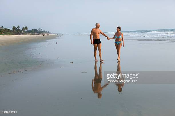 a senior couple going for a stroll on the beach, thailand. - swimwear stock pictures, royalty-free photos & images