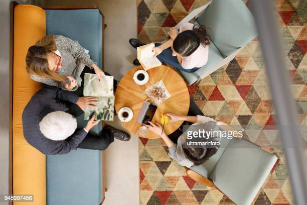 Senior couple,  grandmother and grandfather with his grandchildren  sitting in retro hotel drink coffee and chatting. Active seniors. Directly above. Aerial view of family in cafe.