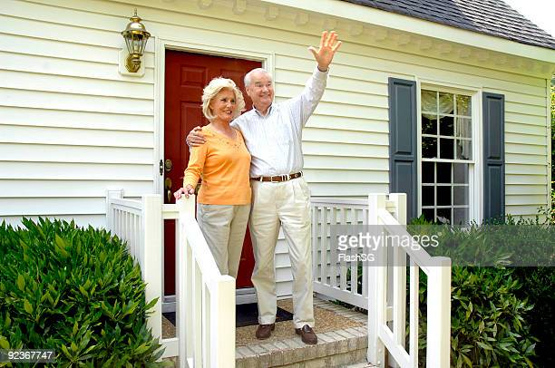 senior couple greeting a vistor to their home - waving stock pictures, royalty-free photos & images