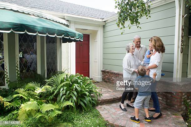 senior couple greeting family at home - family at home stock photos and pictures