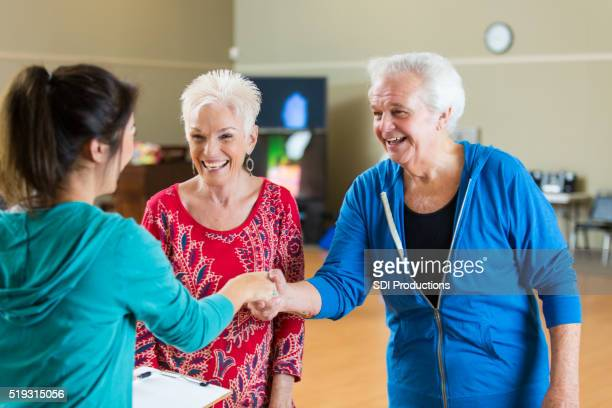 Senior couple greets trainer at gym