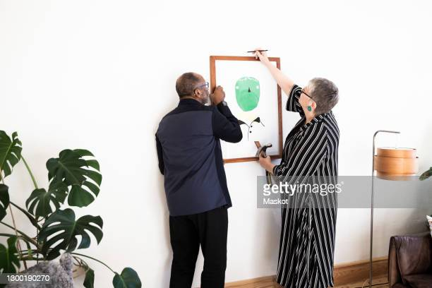 senior couple hanging painting on wall at home - hanging stock pictures, royalty-free photos & images