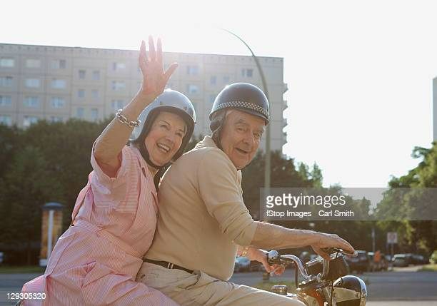 Senior couple happy on motorbike as woman waves