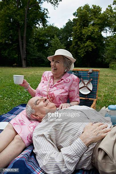 Senior couple have relaxing picnic in the park