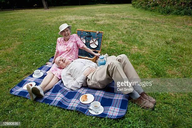 senior couple have relaxing picnic in the park - handen op de buik stockfoto's en -beelden