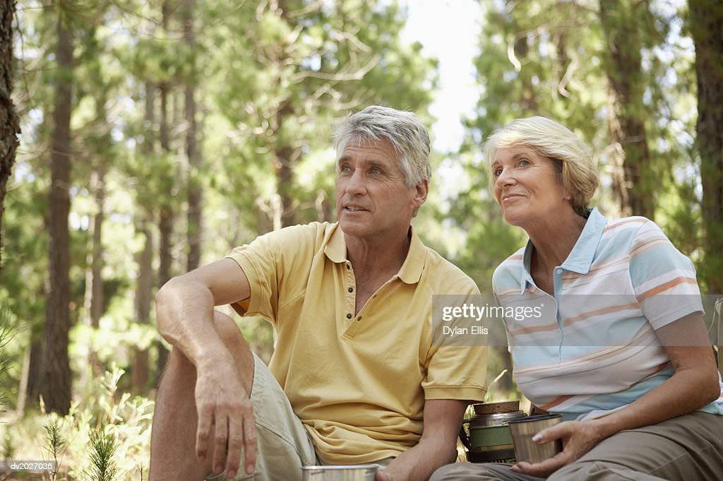 Senior Couple Having a Drink From Their Vacuum Flask in Woodland : Stock Photo