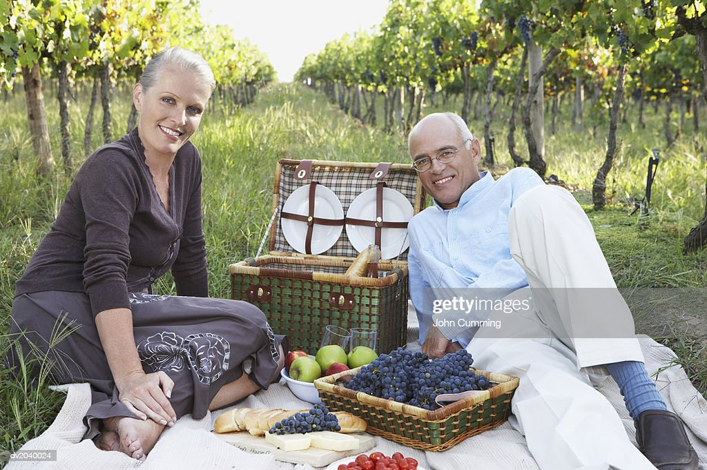 Senior Couple Having a Picnic in a Vineyard : Stock Photo
