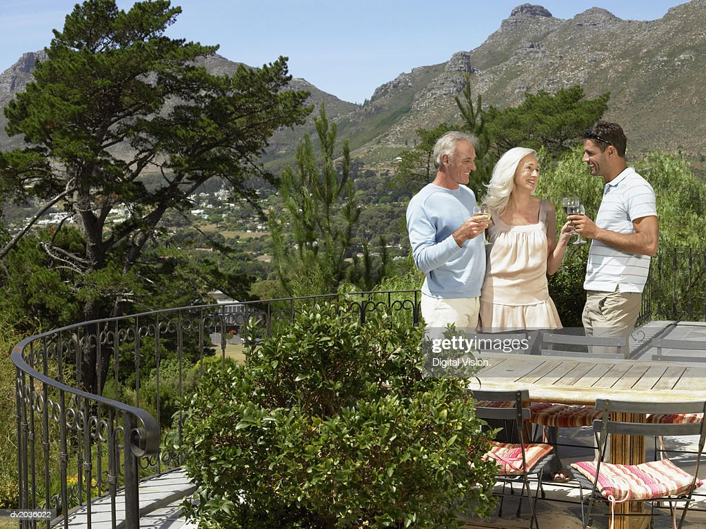Senior Couple Having a Toast of White Wine With Their Son on the Balcony of Their Holiday Home : Stock Photo