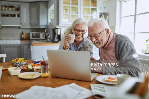 Senior couple having breakfast and using a laptop