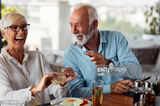 senior couple having breakfast in restaurant - hotel breakfast stock pictures, royalty-free photos & images