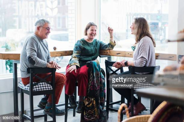 """senior couple having breakfast with friend in a local coffee shop. - """"martine doucet"""" or martinedoucet stock pictures, royalty-free photos & images"""