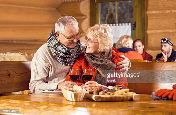 senior couple having dinner in restaurant after skiing - izusek stock pictures, royalty-free photos & images