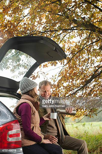 Senior couple having flask of coffee from car boot, Norfolk, UK