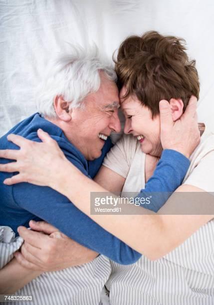 senior couple having fun in bed - erotische umarmung stock-fotos und bilder