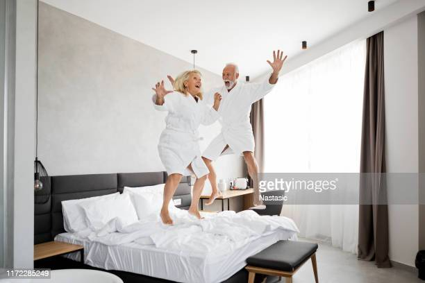 senior couple having fun in hotel room jumping on a bed - jumping stock pictures, royalty-free photos & images