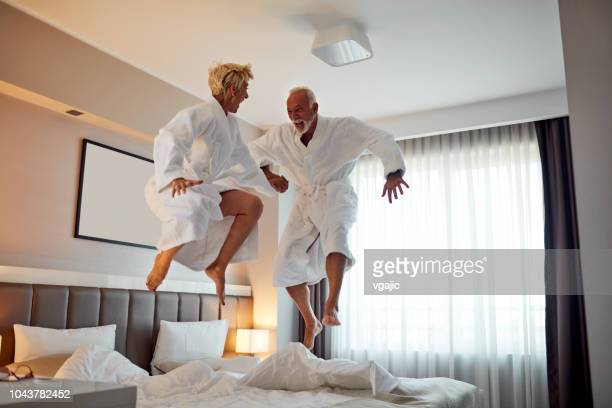 senior couple having fun in hotel room - hotel stock pictures, royalty-free photos & images