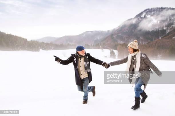 Senior couple having fun in snow-covered landscape
