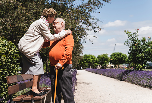 Senior couple having fun in the park, woman standing on bench kissing senior man on forehead - gettyimageskorea
