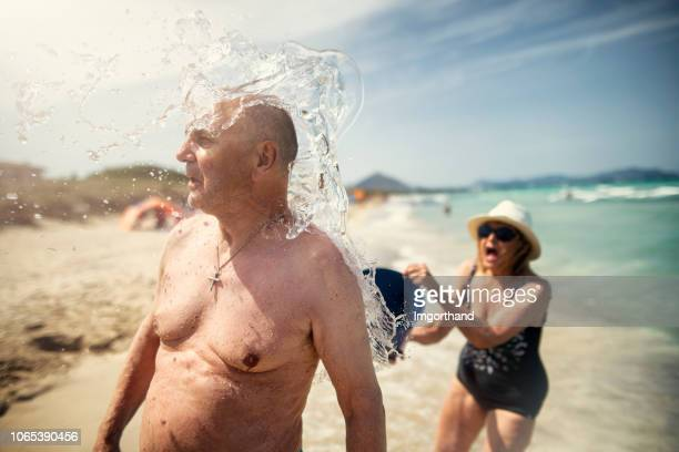 senior couple having fun on a beach - humor imagens e fotografias de stock