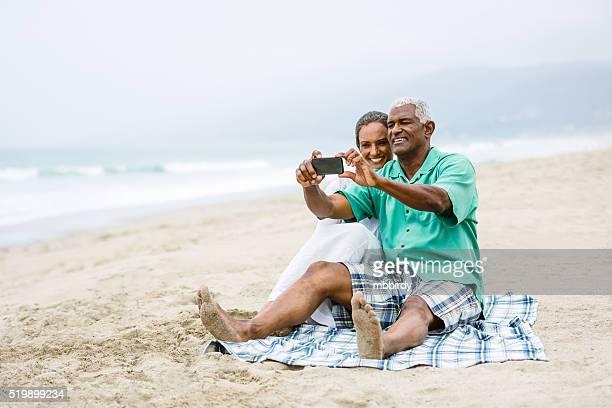 Senior couple having fun with smart phone on beach