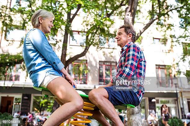 Senior couple having funwith rocker on playground