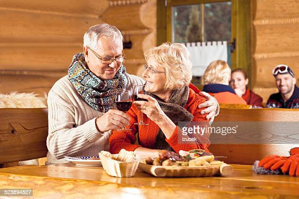 Senior couple having lunch after skiing, toasting wiht wine