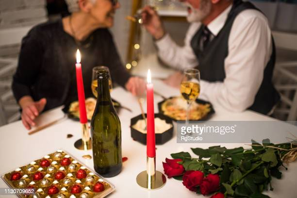 senior couple having romantic dinner - valentines day dinner stock pictures, royalty-free photos & images