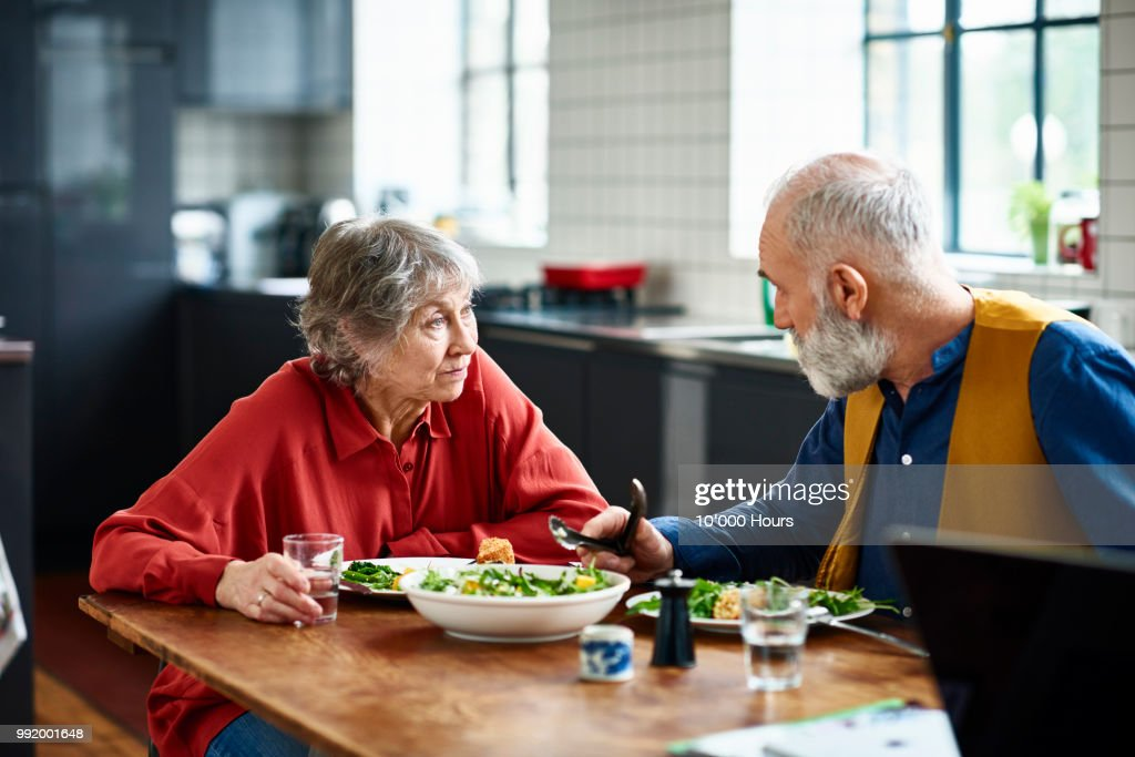 Senior couple having serious discussion over lunch at home : Stock Photo
