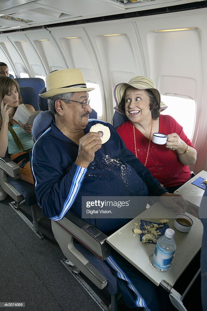 Senior Couple Having Tea and Biscuits on a Passenger Aeroplane : Stock Photo