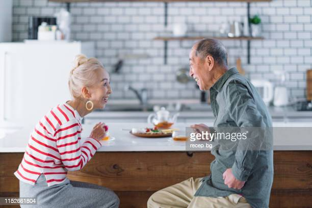 senior couple having tea in kitchen - japanese old man stock pictures, royalty-free photos & images