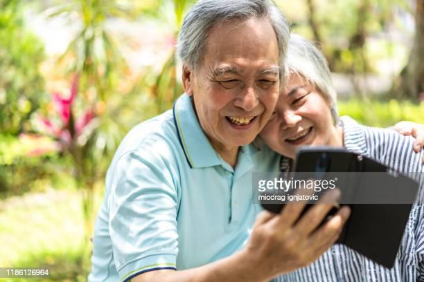 senior paar met video-oproep op mobiele telefoon - aziatische etniciteit stockfoto's en -beelden