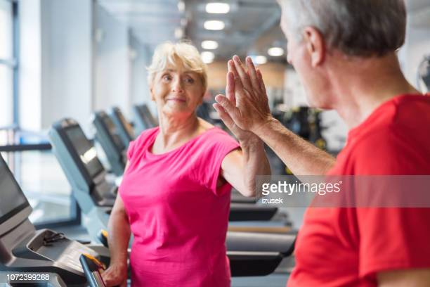 senior couple high fiving at rehabilitation centre - drug rehab stock pictures, royalty-free photos & images