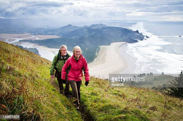 senior couple hiking above coast - coastline stock photos and pictures