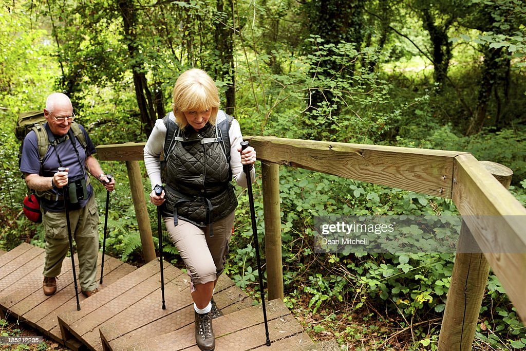 Senior couple hiking with backpacks across countryside
