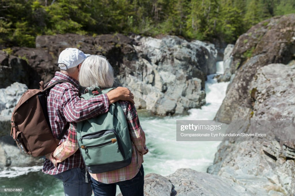 Senior couple hiking in mountains looking at river view : Stock Photo
