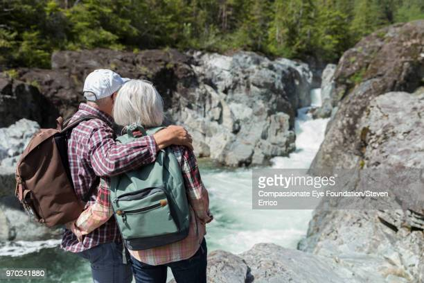 Senior couple hiking in mountains looking at river view